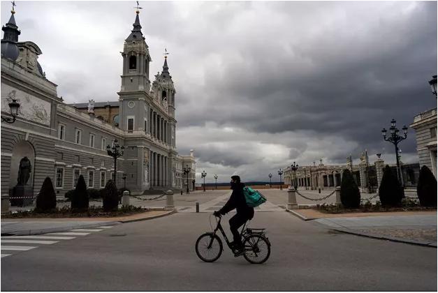 Un homme à vélo sur la Place Royale à Madrid, en Espagne. REUTERS/Juan Medina