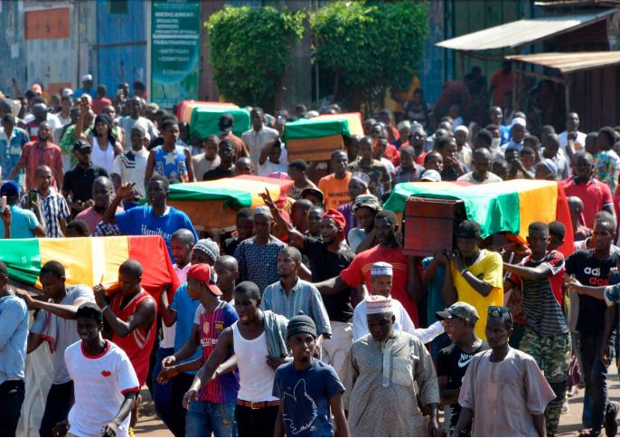 Des personnes portent des cercueils pendant des obsèques après la répression de manifestations de rue, qui a fait au moins 11 morts à Conakry (4 novembre 2019). Le 24 octobre 2019, des foules de manifestant·e·s ont défilé à travers Conakry, la capitale guinéenne, pour protester contre une révision de la Constitution qui devait permettre au président Alpha Condé de briguer un troisième mandat. © CELLOU BINANI/AFP via Getty Images
